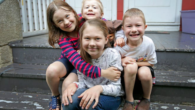 Lilia Graves (front center), 11, sits with her siblings Silvia (clockwise from left), 8, Liam, 3, and Theo, 5, on the porch of their Milwaukee home. Lilia held a yard sale outside her home to help pay the $90 for a Red Cross baby-sitting course, which she hopes to use to watch over her brothers and sister.