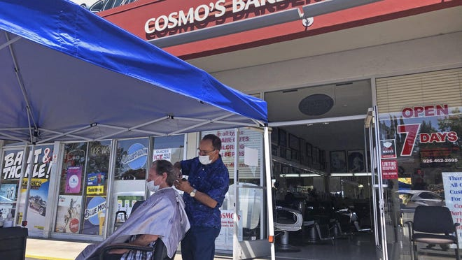 A customer of Cosmo's barbershop receives a haircut in the parking lot in front of the shop Wednesday in Pleasanton.