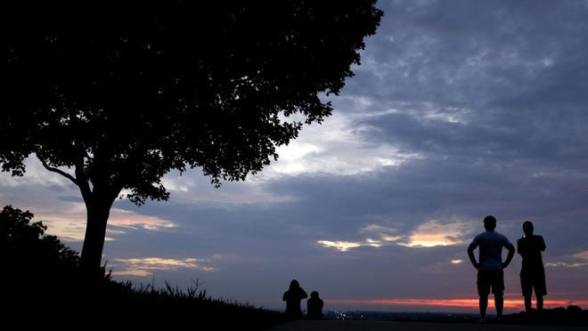 People watch for distant Fourth of July fireworks displays from a park Friday in Kansas City.