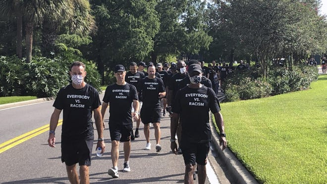 NBA referees march in support of players seeking an end to racial injustice in Lake Buena Vista, Fla., Thursday.