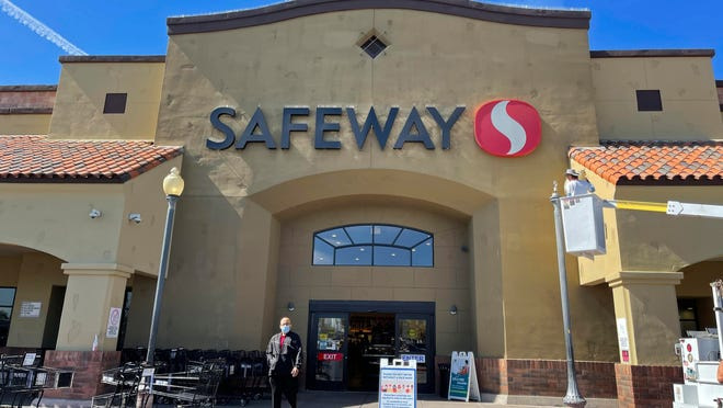 A masked shopper leaves a Safeway supermarket in central Phoenix on Feb. 23.