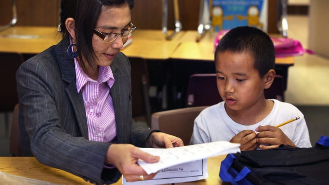 May Oo Mutraw, president of the Burmese Community Center for Education, works on spelling with Ngae Reh, 6, at the center's after-school learning time at Nora Elementary School in Indianapolis on April 15, 2015.