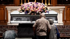 Members of the public walk past the casket of former