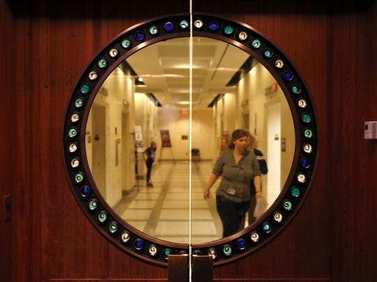 A circular window shows the outside Capitol halls through a sea glass adorned doorway of the chapel on the first floor of the building.