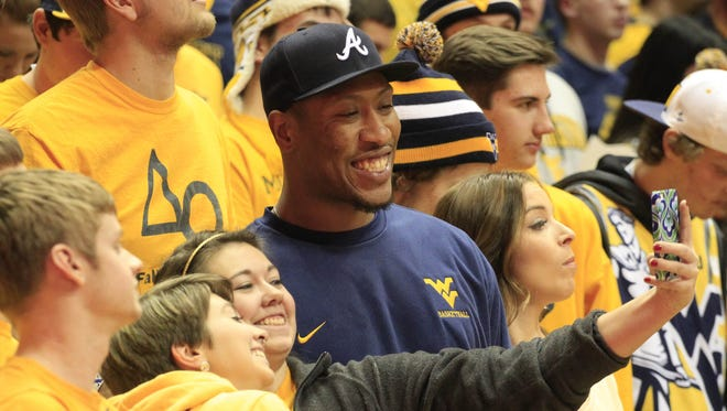 West Virginia Mountaineers fans take a photograph with West Virginia former defensive end Bruce Irvin (R) before the game against the Kansas Jayhawks at the WVU Coliseum.