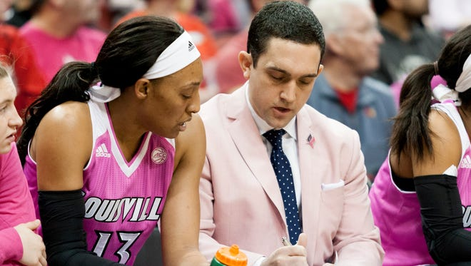 Louisville assistant coach Sam Purcell, right, talks with Cortnee Walton during a game.