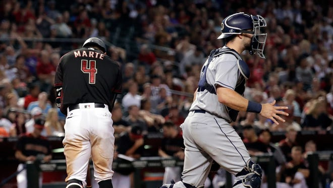 Arizona Diamondbacks Ketel Marte (4) walks to the dugout after striking out to end the game as San Diego Padres catcher Austin Hedges runs to the mound, Saturday, Sept. 9, 2017, in Phoenix. The Padres won 8-7.
