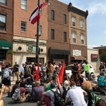 Protesters gather Monday under the Mississippi's state flag hanging from a lamppost on Broad Street in Philadelphia, Pa., demanding that it be removed because includes a Confederate emblem. Monday was the opening day of the Democratic National Convention in the City of Brotherly Love.