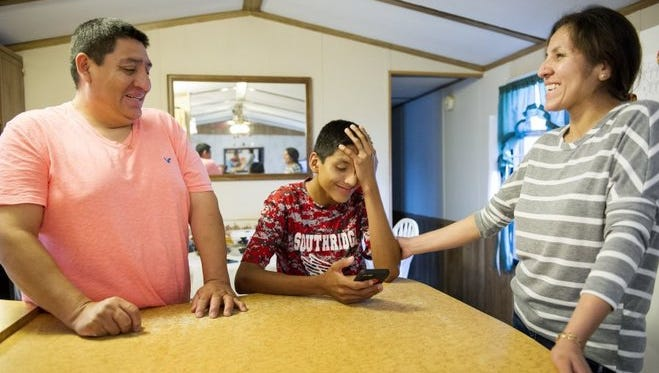 Wences Cruz (left) laughs with his son, Jaffet Cruz, 14, (center) and wife Yessica Valencia in their home in Huntingburg on Thursday. Jaffet will compete against 285 spellers in the Scripps National Spelling Bee, which takes place in National Harbor, Md., May 24-26.