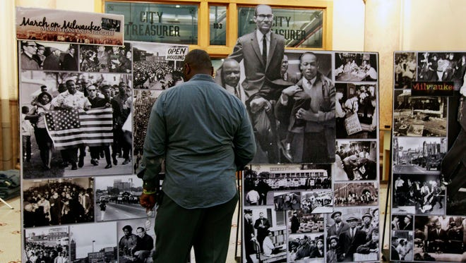 Calvin Jones Sr. views historical photos on display at the 50th anniversary of the fair and open housing marches kickoff ceremony.