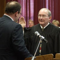 Judge Dee Drell takes the oath of office from his son, Bradley, during his investiture ceremony in 2003. Judge Drell will be inducted into the Louisiana Justice Hall of Fame.
