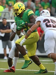 Oregon's Royce Freeman, center, scores a touchdown