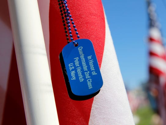 A dog tag for Peter Heinrich hangs on a flag Monday,