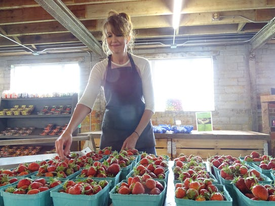Laura Stuckey places a few more strawberries out for