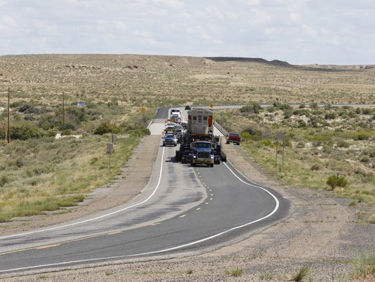 A truck transports a new locomotive for the Navajo