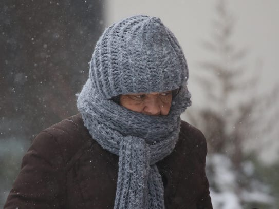 Pedestrians bundled up from the frigid wind and snow