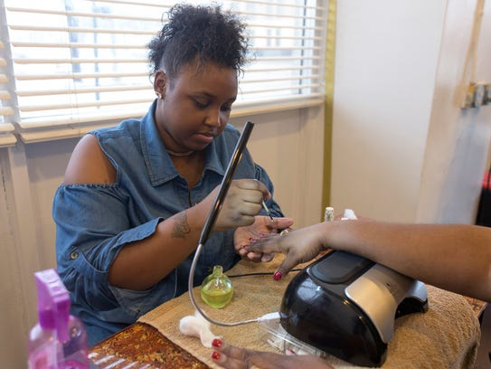 Nail technician Channel Lane of Detroit works on Ayanna
