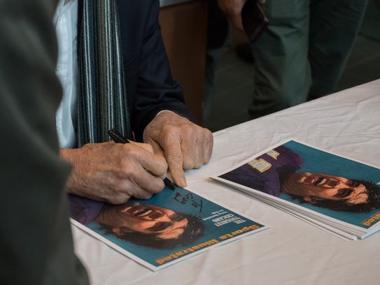Joe Kapp signs printed copies of the infamous Sports