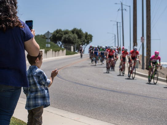 An elementary school student watches the peloton ride