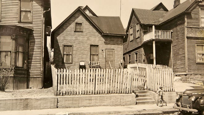 In this historical photo, a young boy sits on a bike on the sidewalk at 2231 Macomb St. on May 3, 1950 in Black Bottom, an area that was torn down in the 1950s to make way for the Chrysler Freeway and the Detroit Medical Center. Black Bottom is the ancestral neighborhood of many metro Detroit African Americans.
