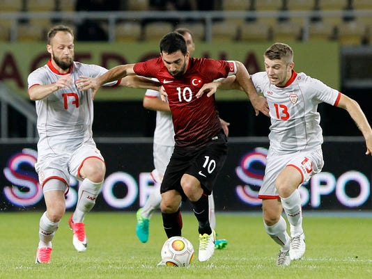 Turkey's Arda Turan, center, is challenged by Macedonia's Stefan Ristovski, right and Ostoja Stjepanovic, left, during an international friendly soccer match at the Philip II National Stadium in Skopje, Macedonia, on Monday, June 5, 2017. (AP Photo/Boris Grdanoski)