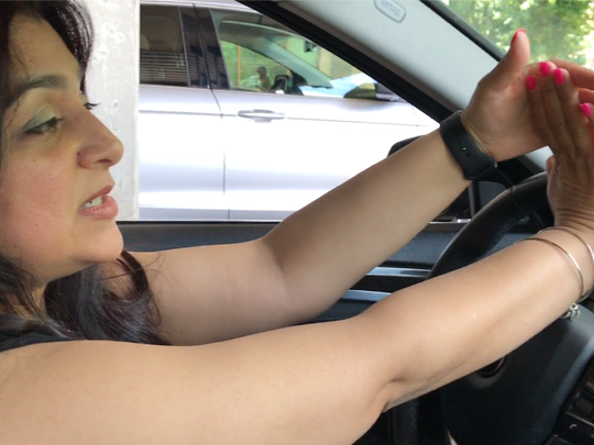 Certified hand therapist Sheena Pasricha demonstrates a relaxing hand stretch in her parked car.