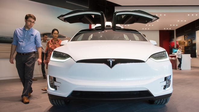 Michael and Janice Breidenbach check out a new Tesla Model X 90D  at the new Tesla store at Waterside Shops in Naples, Fla., on Dec. 20, 2016.