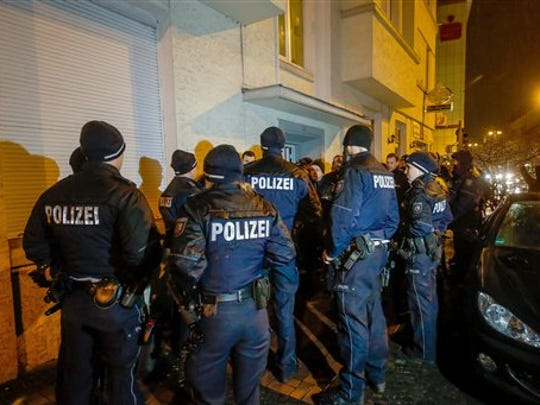 Members of the German police stand in front of a house in Dortmund, Germany, Thursday, Dec. 22, 2016. Several locations across Germany were searched overnight, including a house in Dortmund and a refugee home in Emmerich on the Dutch border, German media reported.
