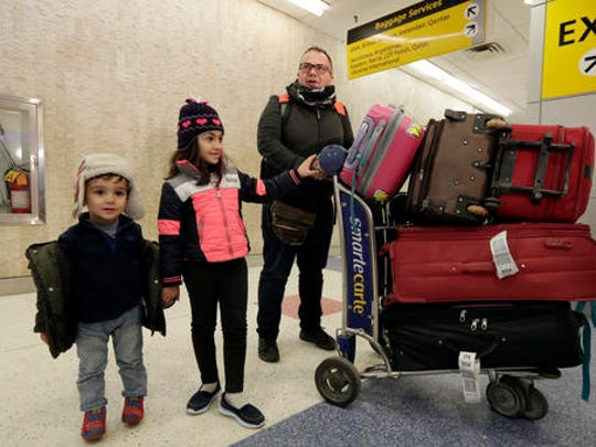 Munther Alaskry, accompanied by his son Hassan, and daughter Dima arrive at New York's JFK International Airport, in New York, Friday, Feb. 3, 2017. Alaskry and his family arrived at New York's Kennedy Airport after the Trump administration reversed course and said he and other interpreters who supported the U.S. military could come to America. They spent nearly a week in limbo in Baghdad, thinking their hopes of starting a new life free from death threats had been shattered.