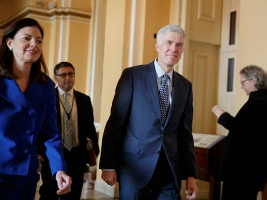 FILE - In this Feb. 2, 2017 file photo, Supreme Court Justice nominee Neil Gorsuch, escorted by former New Hampshire Sen. Kelly Ayotte walks on Capitol Hill in Washington. Gorsuch gave up a $1 million a year paycheck when he left his private law practice a decade ago for less financially rewarding work as a government lawyer and then a judge.