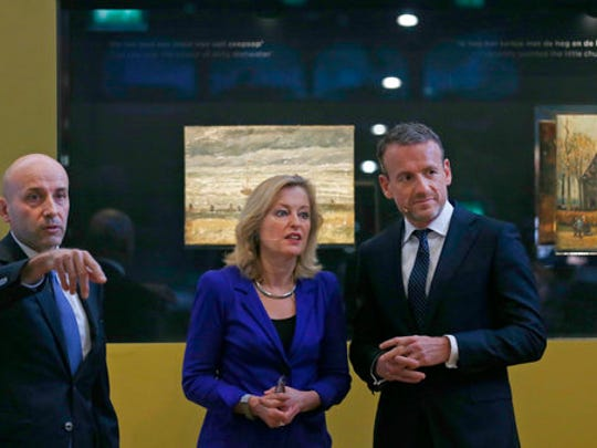 "General Gianluigi D'Alfonso of the Italian Guardia Di Finanza, Jet Bussemaker, Minister for Education, Culture and Science and Van Gogh Museum director Axel Rueger, from left, pose in front of two stolen and recovered van Gogh paintings during a press conference in Amsterdam, Netherlands, Tuesday, March 21, 2017. The two paintings by Dutch master Vincent van Gogh titled ""Seascape at Scheveningen"" (1882) and ""Congregation leaving the Reformed Church in Nuenen,"" (1884-1885) returned to the Amsterdam museum after they were stolen from in a nighttime heist 15 years ago and recovered by Naples police in Italy."