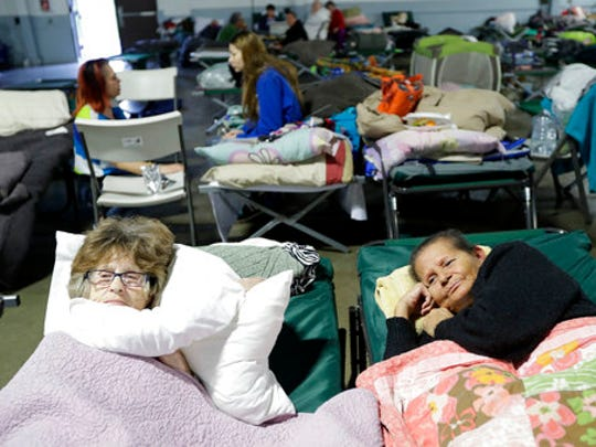 FILE - In this Feb. 13, 2017, file photo, Delores Dearte, right, and Merna Thompson, neighbors from the town of Gridley, Calif., rest at a shelter for evacuees from cities surrounding the Oroville Dam, in Chico, Calif. Nearly 200,000 people downstream from California's Oroville Dam had to be evacuated for fear it would release a catastrophic torrent of water.