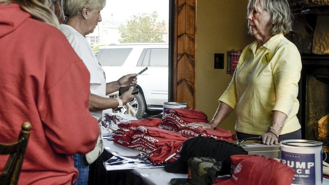 Emily Wellman sells merchandise for President Donald Trump's reelection campaign Friday in Garden City at the traveling Pop-Up for Trump Roadshow at the Clarion Inn.