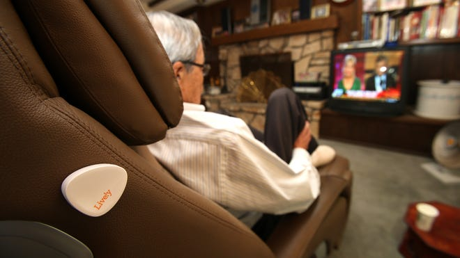 Song Pak, who is 80, sits in his massage chair to watch TV. It has a small Lively transmitter attached. Lively's remote units sense movement  by the owner and can alert loved ones if something is not trending normally.