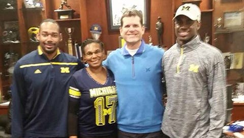 Wide receiver recruit Jeremiah Holloman, right, and Michigan football coach Jim Harbaugh (light blue shirt) pose for a photo.