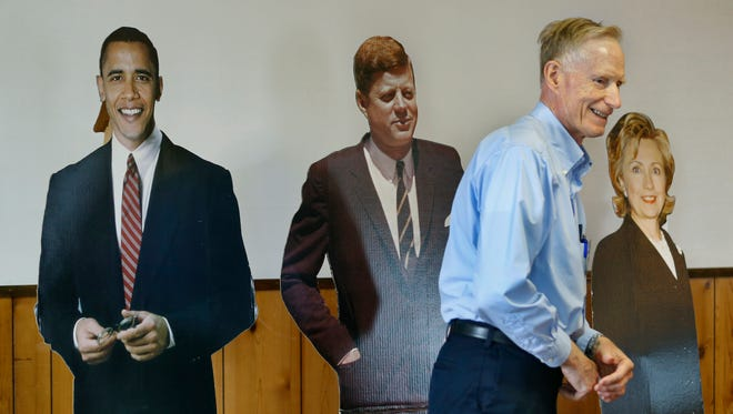 """John Loser, with the Riga Democratic Committee walks in front of cutouts of political celebrities during an """"Undecided Rally for Bernie Sanders and Hillary Clinton"""" at the American Legion Post on Buffalo Road in Riga."""