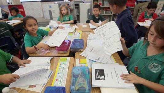 Cahuilla Elementary second grade students tear out a math homework assignment from their workbooks.