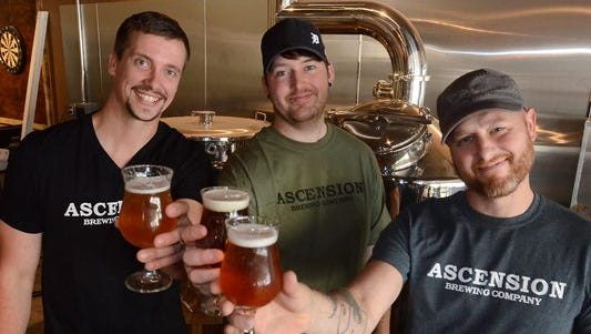 Owners and managers of Novi's Ascension Brewery -- (from left) Adam Czap, Joey Hansen, and Jeremiah Lynch -- raise a glass to their July 24 opening at 42000 Grand River Avenue.