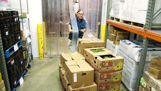 William Ziegler stores fresh produce in a walk-in cooler in Food Finders Food Bank. Food pantries expect increased need as a result of changes in SNAP eligibility.