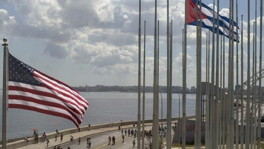 The U.S. flag waves outside the U.S. Embassy near a Cuban flag overlooking Havana's seaside boulevard in Cuba.