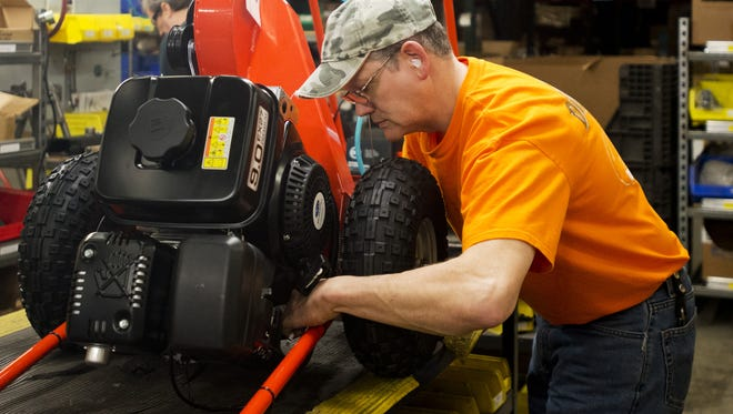 Harold Townsend, an assembly worker at DR Power Equipment, works on a machine at their Winooski manufacturing plant in March 2013.