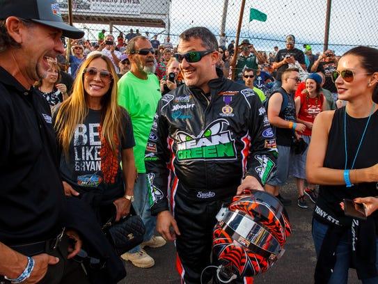 Former NASCAR driver Tony Stewart (center) talks with