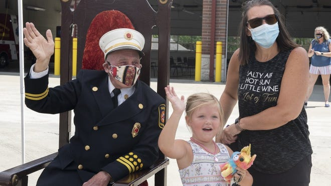 Suffield Township Fire Department celebrated Fire Capt. Robert Dudley's 50 years of service with a parade of trucks from local departments. He currently has no plans to retire. Pictured, Dudley waves at the people in the lineup from a velvet covered chair on Thursday. With him is daughter, Brenda Wagner, and great-granddaughter, Payton Winter, 4.