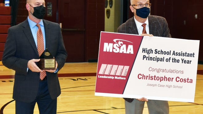On Wednesday, Joseph Case High School Assistant Principal Chris Costa, left received his award as Massachusetts School Administrator Association's 2020 Assistant Principal of the Year. Case Principal Brian McCann, right, holds up a banner announcing the award.