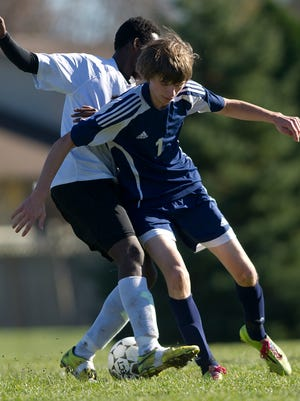 Columbus Catholic's Charles Payant, right, and Barron's Abdalla Ali go after the ball during the division 4 sectional final soccer playoff at Griese Park in Marshfield, Saturday, Oct. 25, 2014.