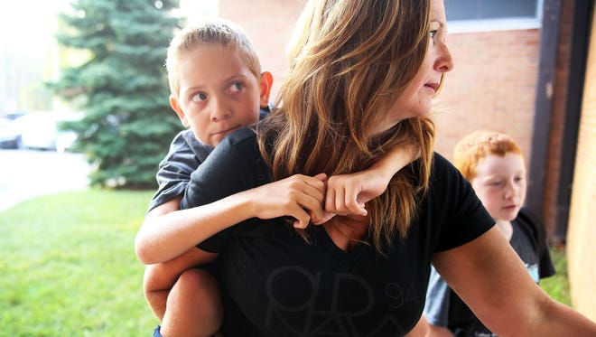 Danielle Gandee helps her son Braden  Gandee by carrying him on her back to his  third grade classroom  on the first day of school at Douglas Road Elementary in Lambertville, Mich. Tuesday, Sept. 8, 2015.  His younger brother Kellen Gandee, a second grader carries both of their book bags into school. Braden  has cerebral palsy and recently had surgery with the hopes that in the near future he will walk on his own one day. For now he still is assisted by his family, a walker and a chair. His older brother raised awareness for cerebral palsy by walking many miles with him on his back.