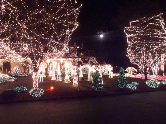 The full moon is pale in comparison to the light of Christmas decorations at this Victoria Lane home. Mel Evans/The Record