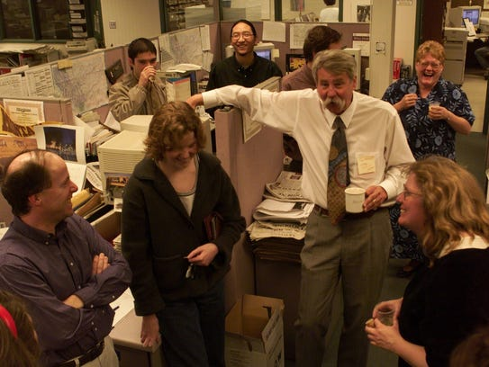 Eric Newhouse, Great Falls Tribune projects editor, is surrounded by well-wishers in the newsroom on April 10, 2000, after receiving word he had won the Pultizer Prize for explanatory reporting. Left to right are Jim Strauss, Take Uda, Karen Ivanova, Nick Daniels, Newhouse, Carrie Koppy and Kathleen Schultz.