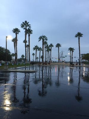 Rain dampens The Desert Sun parking lot and clouds obscure Mt. San Jacinto Wednesday in Palm Springs.