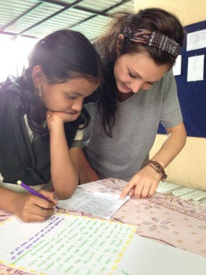 Social work student Kenzie Bohm, right, works with a girl in India on a photo narrative project.